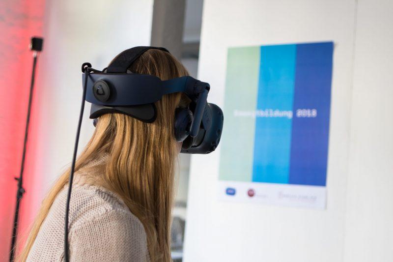 """Frau mit VR-Brille, im Hintergrund ein Poster mit den Bewegtbildungsfarben mint, blau und dunkelblau und dem Schriftzug """"Bewegtbildung 2018"""""""