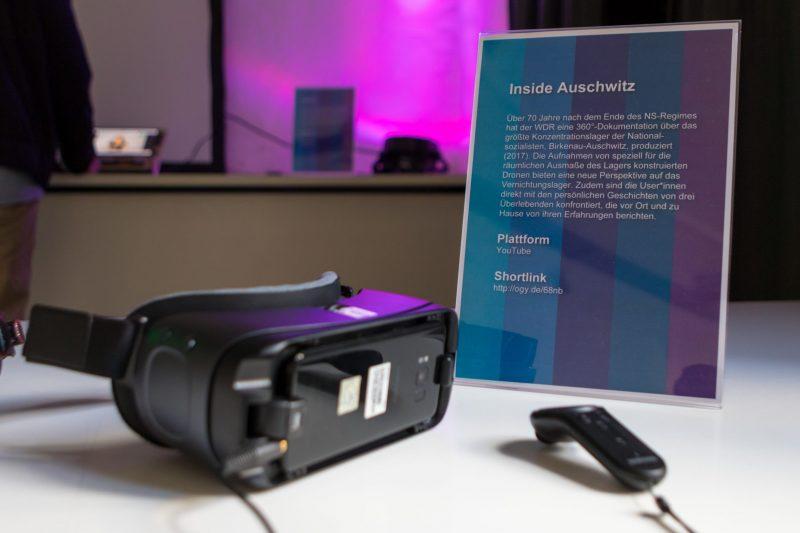"""Eine VR-Brille und ein VR-Controller liegen neben einem Aufsteller mit der Beschreibung für das VR-Projekt """"Inside Auschwitz"""""""