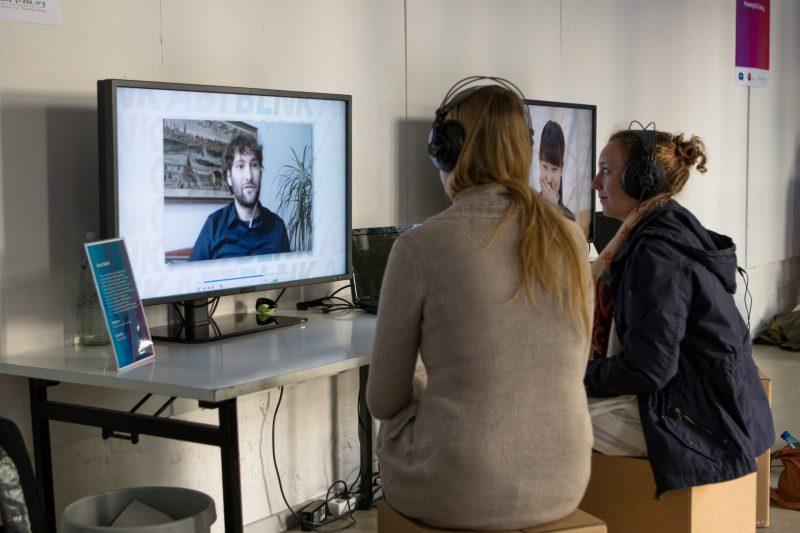 Zwei Frauen mit Kopfhörern sitzen vor einem Bildschirm, auf der das Gesicht eines Mannes in einem Videokonferenzfenster zu sehen ist.