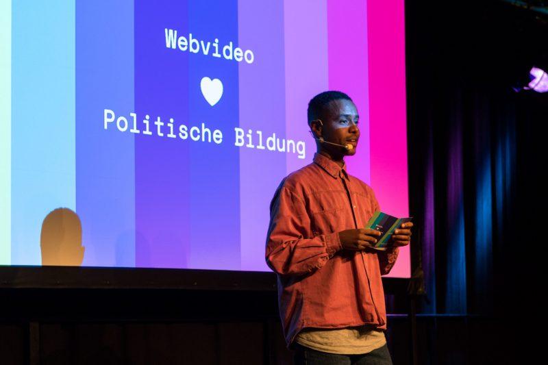 """Tarik Tesfu, YouTuber, hält einen Vortrag auf der Fachtagung Bewegtbildung 2018 vor dem Logo der Fachtagung, auf dem steht """"Webvideo, gefolgt von einem Herz, gefolgt von den Worten """"politische Bildung"""""""