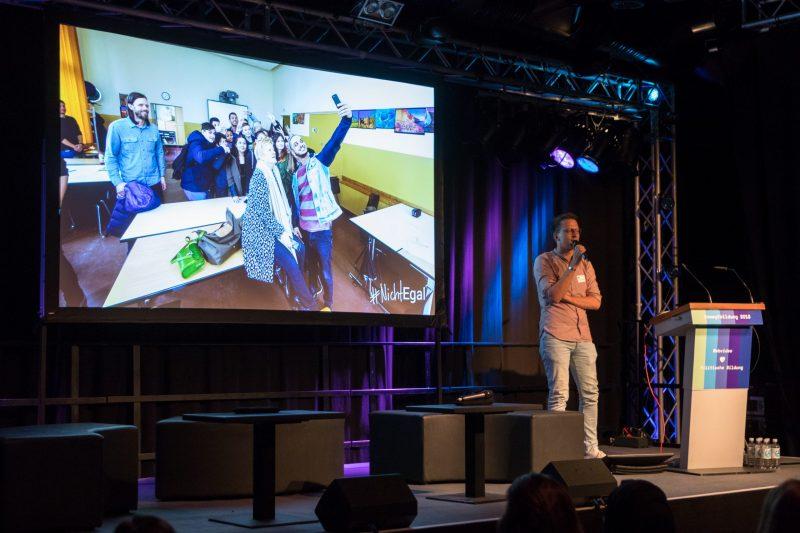 Björn Schreiber von der FSM steht auf der Bühne der Fachtagung Bewegtbildung 2018, hinter ihm ist ein Foto auf der Leinwand, auf der Younis von den Datteltätern ein Selfie mit einer Schüler*innengruppe im Rahmen des Projektes #NichtEgal macht