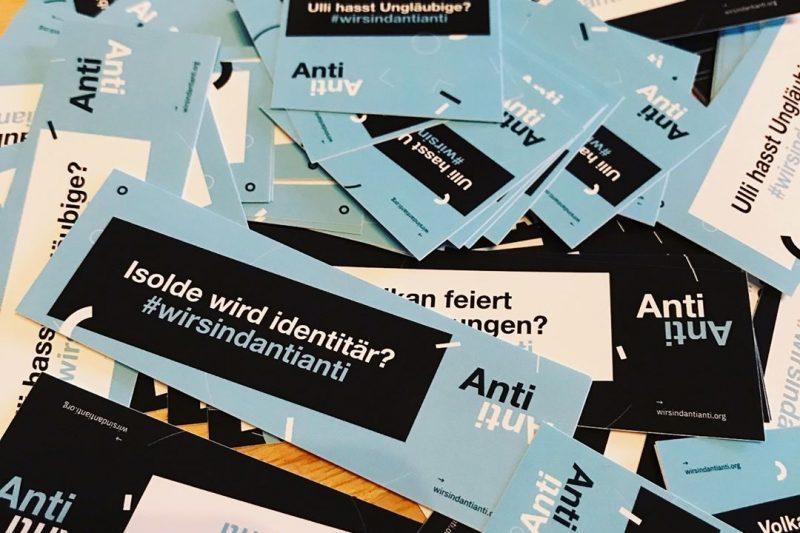 Es sind verschiedene Sticker des Projekts AntiAnti zu sehen. Die verschiedenen Sprüche beziehen sich auf die Radikalisierung von Jugendlichen. Unter allen findet sich der Hashtag #wirsindantianti