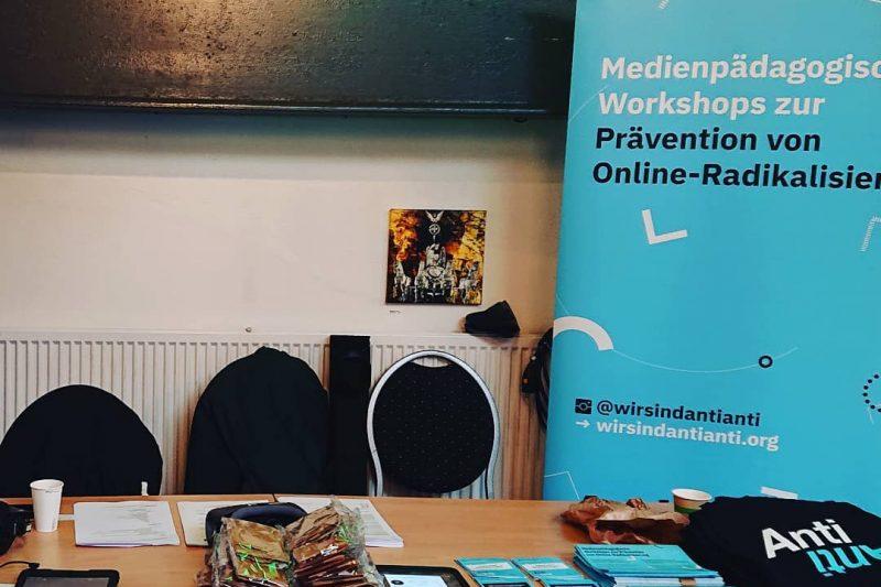 Auf dem Bild erkennt man den AntiAnti-Stand auf dem Berliner Jugendforum 2019. Es ist ein Tisch zu sehen, auf dem Sticker, iPads und Beutel ausliegen. Im Hintergrund steht der AntiAnti-Aufsteller.