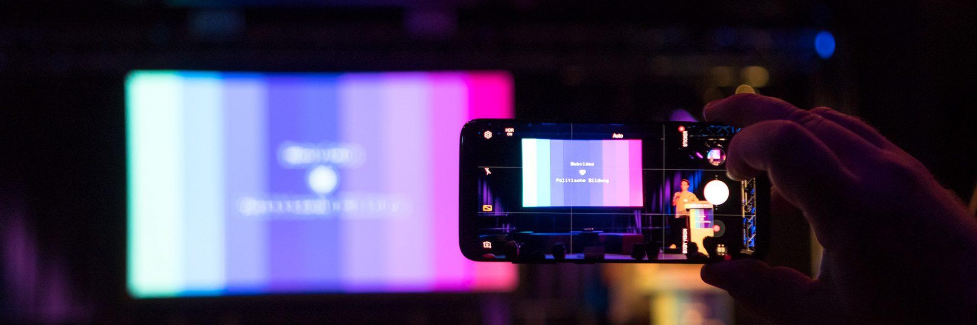 Kamerabildschirm filmt eine große Leinwand ab, auf dem das Logo und die Farben von Bewegtbildung.net zu sehen sind.