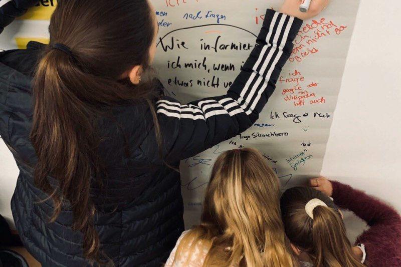 Zwei jugendliche Workshopteilnehmerinnen beschreiben ein Plakat zu der Frage, wie sie sich informieren, wenn sie über ein Thema nicht Bescheid wissen.