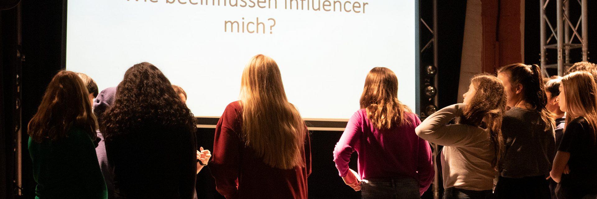 """Sechs Mädchen stehen mit dem Rücken zur Kamera und schauen auf eine Leinwand, auf der die Frage """"Wie beeinflussen Influencer mich"""" steht."""