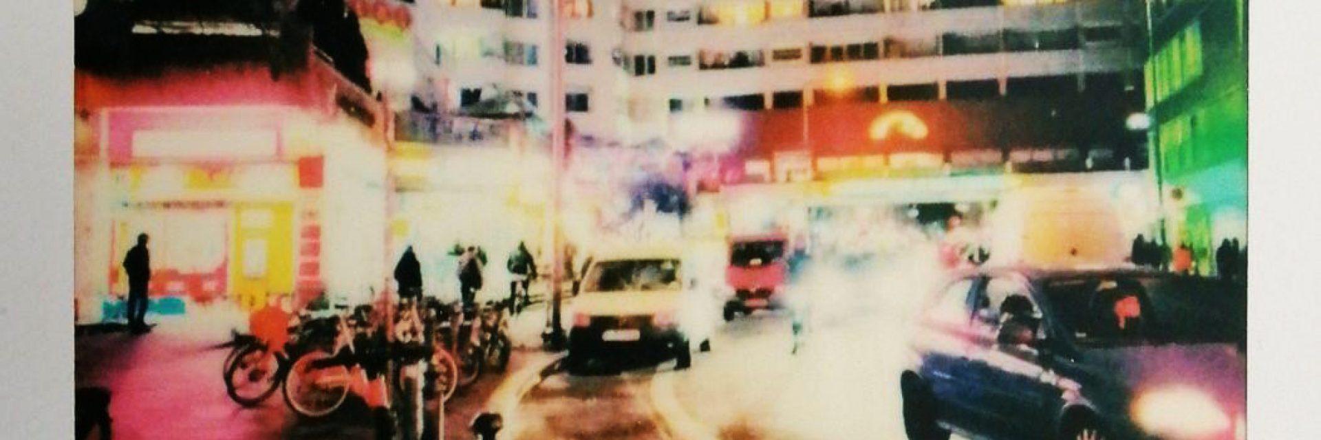 Eine Polaroidaufnahme des Kottbusser Tors bei Nacht. Unten ist das Logo des Projekt kiez:story zu sehen.