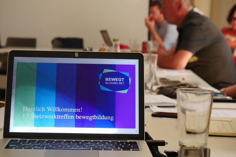 """Computerbildschirm zeigt das Bewegtbildungslogo und den Text """"Herzlich willkommen! 15. Netzwerktreffen Bewegtbildung. Im Hintergrund sieht man zwei Menschen an einem Konferenztisch sitzen."""
