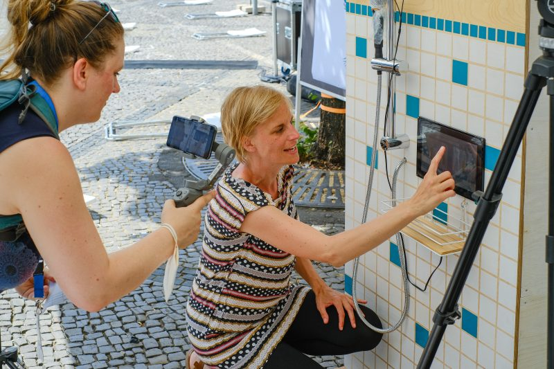 Frau erklärt das Exponat der Singdusche, andere Frau filmt mit dem Handy
