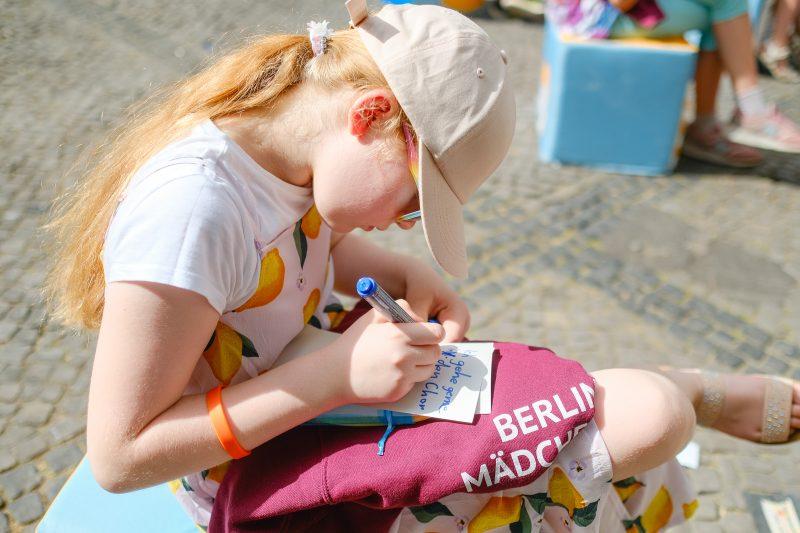 Mädchen mit Sweater vom Berliner Mädchenchor schreibt auf eine Moderationskarte