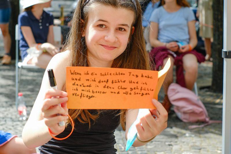Mädchen hält beschriebene Moderationskarte in die Kamera, auf der sie schreibt, dass ihr Musik hilft, wenn sie schlechte Laune hat.