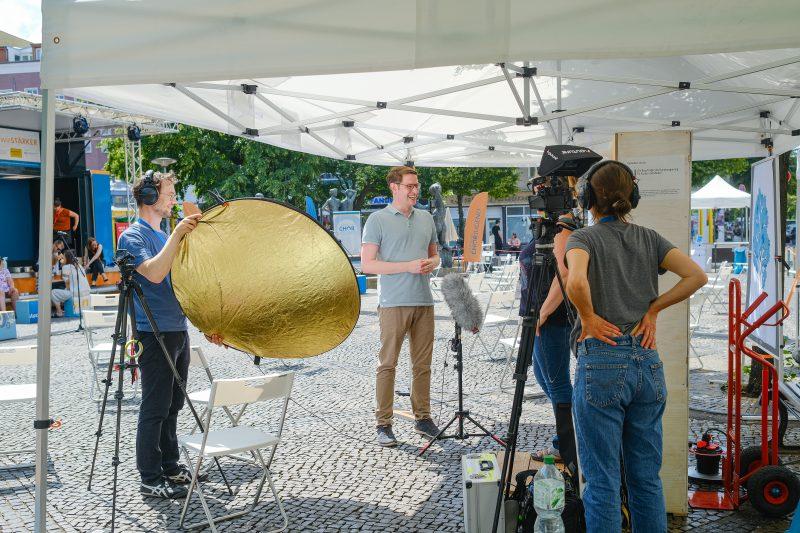 Frau hinter einer Kamera filmt ein Interview zwischen einem Mann und einer Frau, ein weiterer Mann hält eine Sonnenblende.