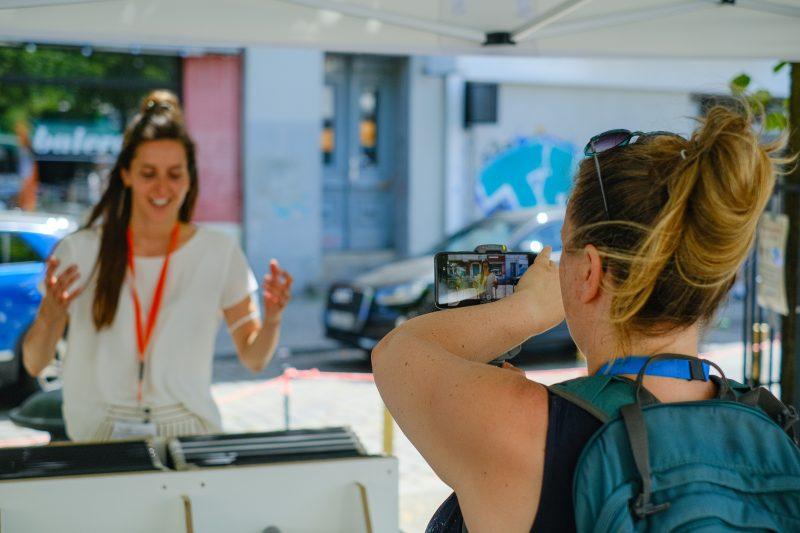 Eine Frau erklärt ein Exponat der Singbusausstellung, eine andere Frau filmt sie mit dem Handy.